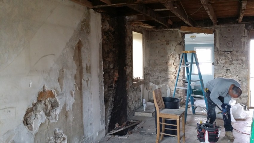 A kitchen stripped down to the dry wall with a man bending over working with tools.