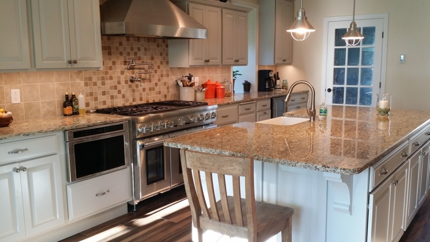 A white kitchen with tan countertops and tile backsplash, stainless steel appliances; photo taken at eye-level.