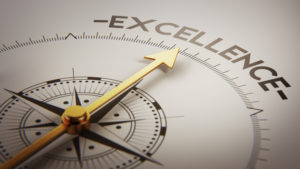 """A compass with a golden needle points toward the word """"Excellence"""" in the upper right of the compass circle."""